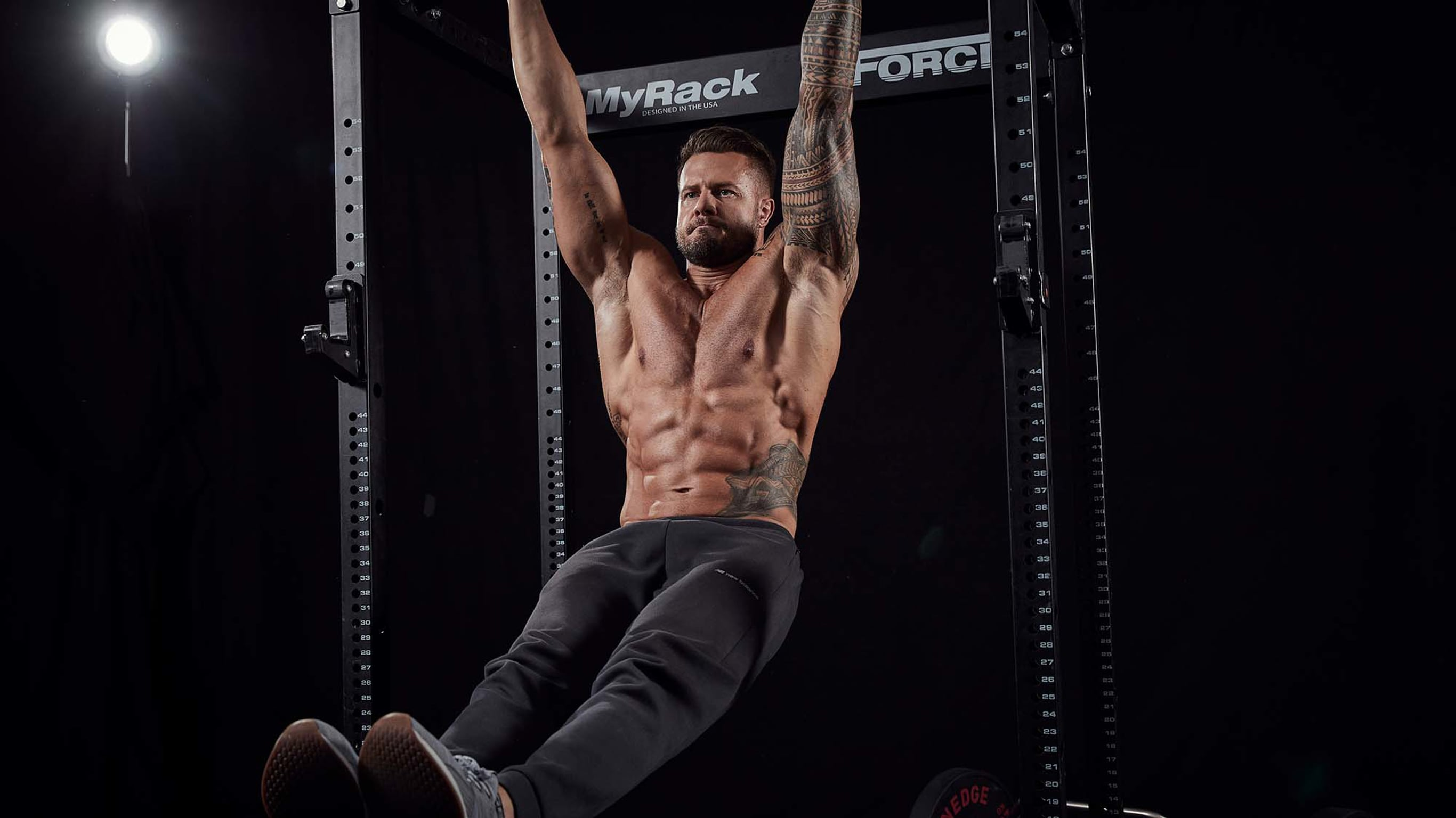A shirtless, muscular man with visible abs hanging from a pull-up bar.