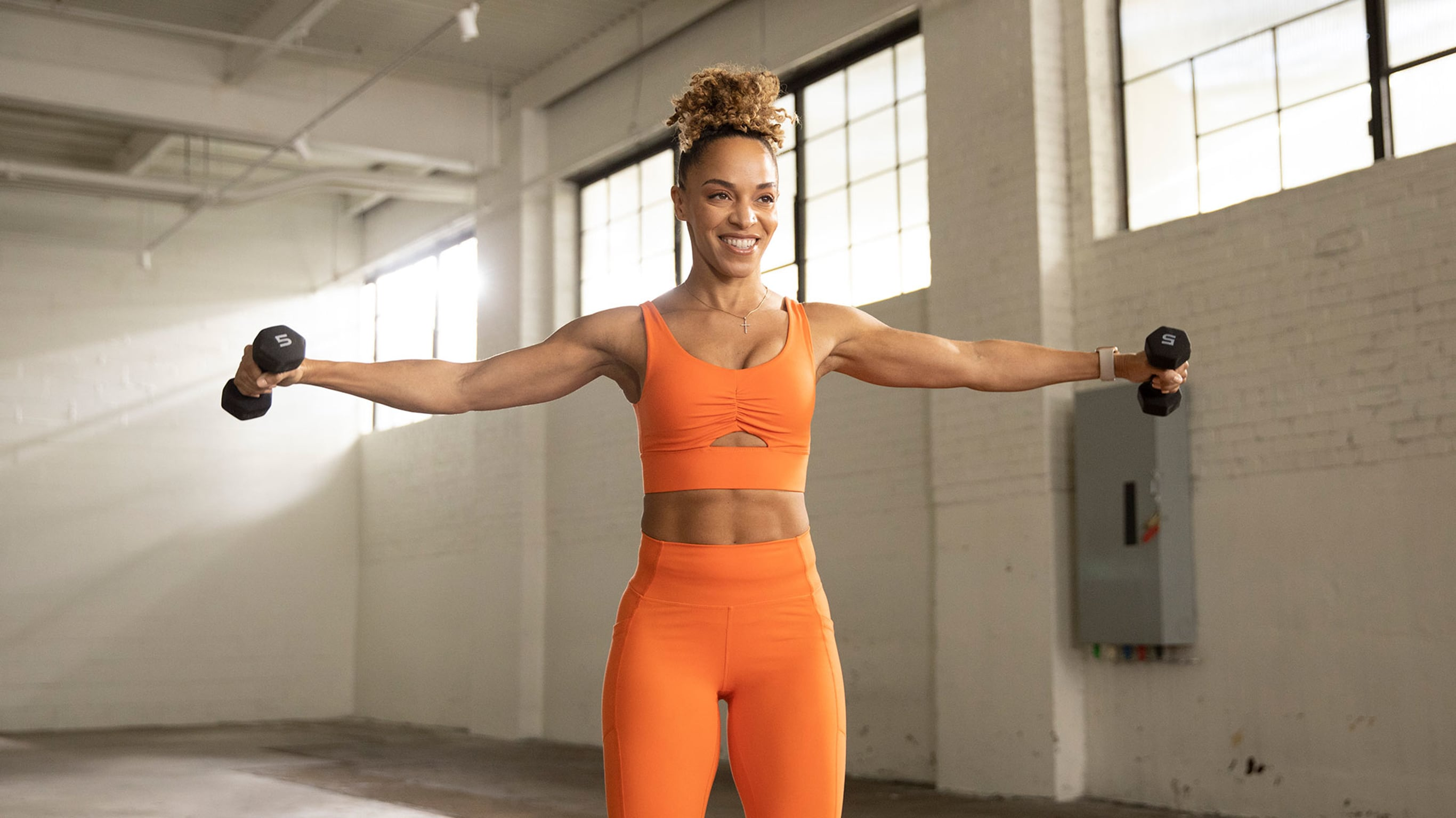 A woman in orange workout gear performing a lateral raise with dumbbells.